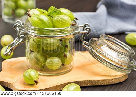 Glass Jar With Green Gooseberries On Board. Gray Napkin. Dark Wooden Background. Top View