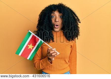 African american woman with afro hair holding suriname flag scared and amazed with open mouth for surprise, disbelief face