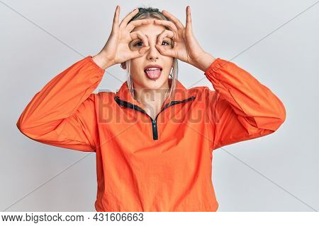 Young modern girl wearing sports sweatshirt doing ok gesture like binoculars sticking tongue out, eyes looking through fingers. crazy expression.