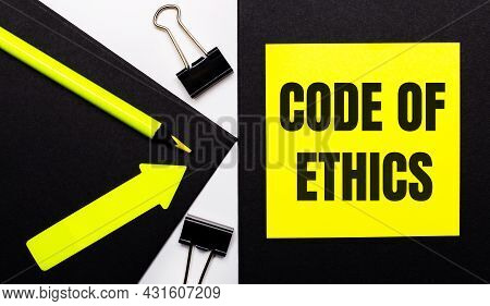 On A Black Background, A Bright Yellow Pencil And An Arrow And A Yellow Sheet Of Paper With The Text