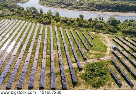 Aerial View Of Solar Power Plant On Green Field. Electric Farm With Panels For Producing Clean Ecolo