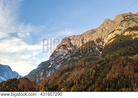 Aerial View Of Majestic European Alps Mountains Covered In Evergreen Pine Forest In Autumn.