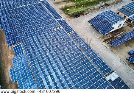 Aerial View Of Blue Photovoltaic Solar Panels Mounted On Industrial Building Roof For Producing Gree