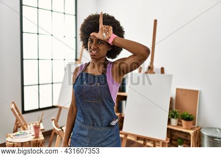 Young african american woman with afro hair at art studio making fun of people with fingers on forehead doing loser gesture mocking and insulting.