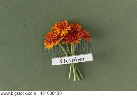 Calendar Autumn Month October And Orange Flowers On Green Background. Top View Flat Lay. Minimal Con