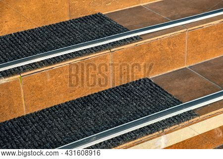 Closeup Of Ceramic Tiles Covering Porch Stairs With Rubber Anti Slippery Stripes On It.
