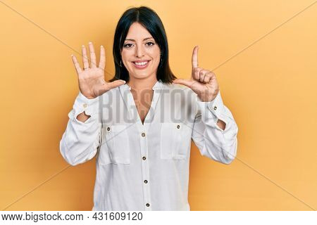 Young hispanic woman wearing casual clothes showing and pointing up with fingers number seven while smiling confident and happy.