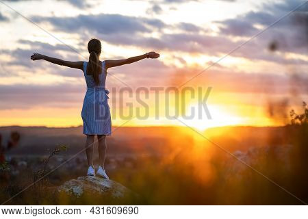 A Young Woman In Summer Dress Standing Outdoors With Outstretched Arms Enjoying View Of Bright Yello