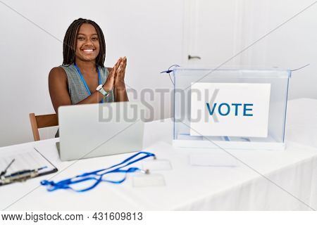 Young african american woman working at political election sitting by ballot clapping and applauding happy and joyful, smiling proud hands together