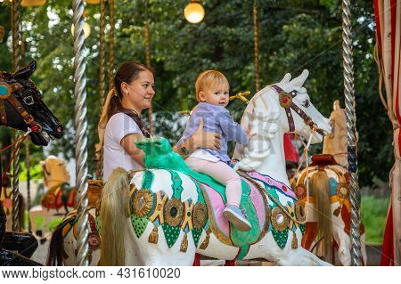 Cute Baby Girl With Mother On The Horse Of Old Retro Carousel, Prague, Czech Republic