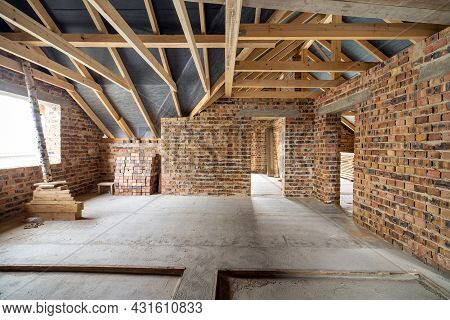 Interior Of Unfinished Brick House With Concrete Floor, Bare Walls Ready For Plastering And Wooden R