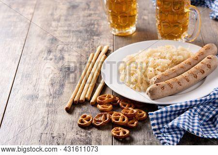 Bratwurst Sausage ,sauerkraut, Pretzels And Beer On Wooden Table. Typical German Food