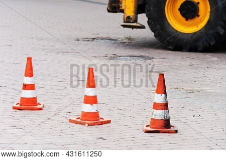 Traffic Cones On The Background Of An Excavator Wheel. Roadworks Concept In City