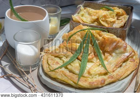 Homemade Sweet Frying Roti (cannabis Pancake) With Cannabis Served With Cannabis Tea On Ceramic Plat