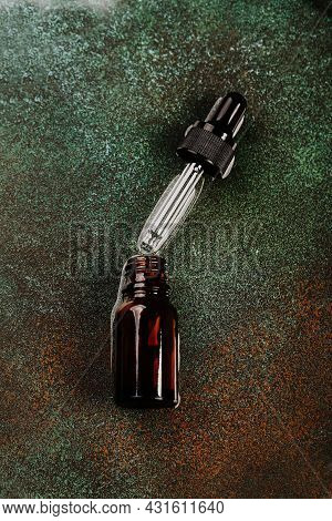 Abstract Cosmetic Laboratory. Bottles Of Dark Amber Glass On A Green Podium Background. Natural Cosm