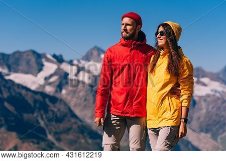 A Traveling Couple In Hiking Gear Against The Background Of Mountains. Two Tourists On The Top Of Th