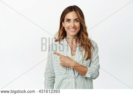 Ambitious Business Woman Smiling, Pointing Finger Left At Company Logo, Banner Or Sale Promotion, St