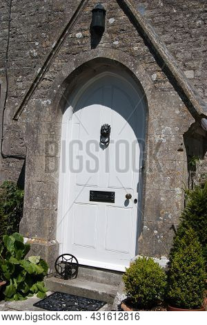 A Close-up Of An Arched Doorway Painted White Set In A Purbeck Stone House