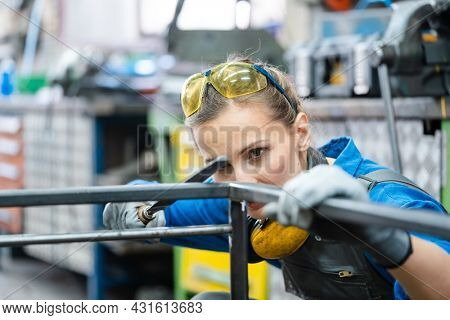 Woman metalworker checking the accuracy of her work