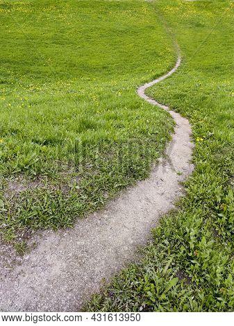 A Walking Winding Path On A Hill Among Green Grass.