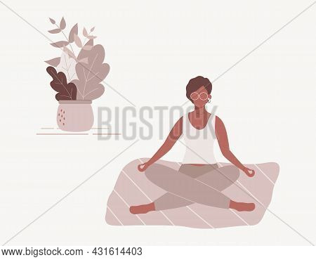 Afro-american Woman Sitting With Her Legs Crossed On Floor And Meditating. Young Lady In Yoga Postur