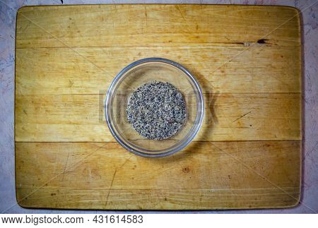 Black Ground Pepper In A Glass Bowl On A Wooden Board For Cutting Food
