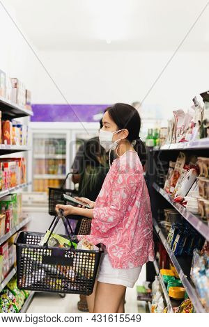 Asian Woman With Protective Face Mask With Shopping Basket In Department Store