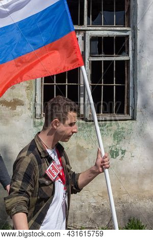 Young Caucasian Man Carrying Russian Tricolor Flag In Front Of Broken Window With Steel Bars At Poli