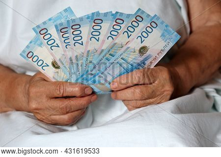 New Russian Rubles In Wrinkled Female Hands Closeup, Elderly Woman With Money Sitting In Bed. Concep