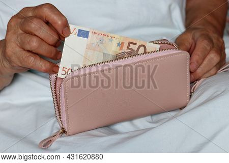 Elderly Woman Takes Out A Euro Note From Her Wallet Sitting In Bed. Concept Of Pension Payments, Pai