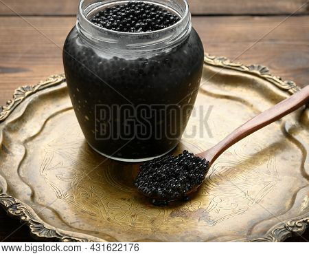 Fresh Black Paddlefish Caviar In A Wooden Brown Spoon And A Full Can Of Caviar On A Wooden Table, De