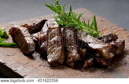Roasted Piece Of Beef Ribeye Cut Into Pieces On A Vintage Brown Chopping Board, Rare Doneness. Appet