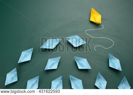 Group Of Blue Paper Boats Are Sailing In One Direction, One Yellow Is Sailing In The Opposite Direct