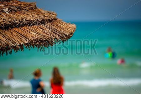 Soft Focus Photo of a Beach. People Spending Time on the Seashore. Summer Vacation Conceptual Background.