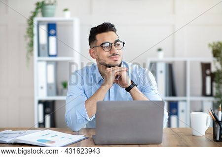 Dreamy Arab Guy In Glasses Sitting At Laptop At Office, Looking Aside, Taking Break From Online Job