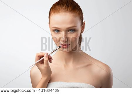 Female Arm Making Makeup For Red-haired Female Model, Gray Background