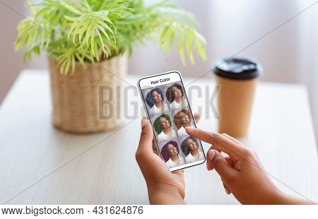 African-american Woman Checking Hair Color Simulation Mobile App On Smartphone