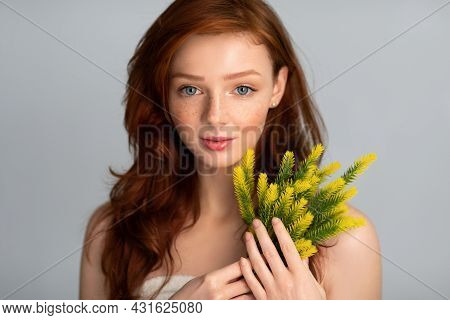 Tender Red-haired Female Posing Holding Plant Standing Over Gray Background