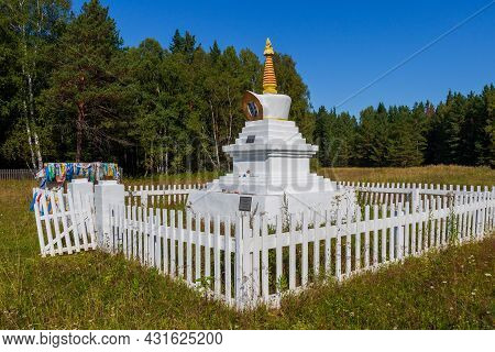 Ritual Buddhist Stupa Of A Enlightenment Behind A White Wooden Fence On Green Meadow Against Forest
