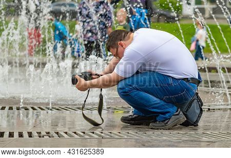 A Guy, A People, A Man Photographer Is Sitting And Holding A Digital Slr Camera In A Uncomfortable P