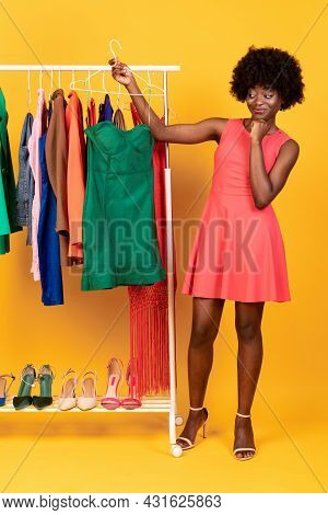 African Shopaholic Lady Shopping Holding Hanger With Dress, Yellow Background