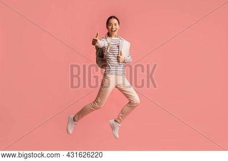Happy Young Asian Female Student Jumping In Air And Showing Thumb Up