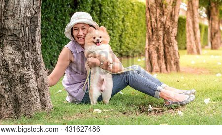 Dog With Owner Concept -  Asia Women Sitting On Grass Under A Tree In The Garden With Lovely Puppy P