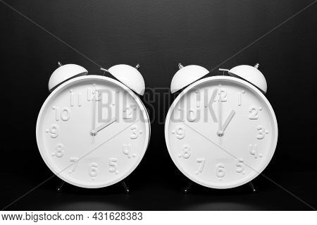 Daylight Saving Time Concept. Two White Retro Clock Isolated On Black Background. Copy Space