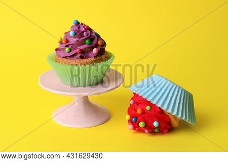 Dropped And Good Cupcakes On Yellow Background. Troubles Happen