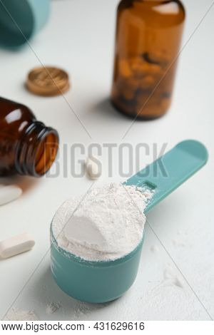Measuring Scoop Of Amino Acids Powder On White Table