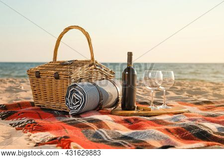Blanket With Picnic Basket, Corkscrew, Bottle Of Wine And Glasses On Sandy Beach Near Sea