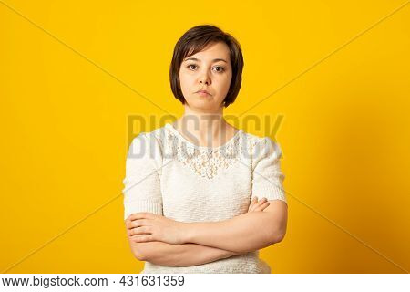 Angry Grumpy Female Dressed Casually Keeping Arms Folded, Looking At Camera With Strict And Skeptica