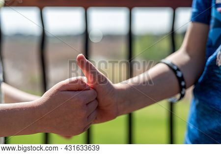 Two Children Playing A Thumb War Battle With The Objective To Pin The Opposing Players Thumb