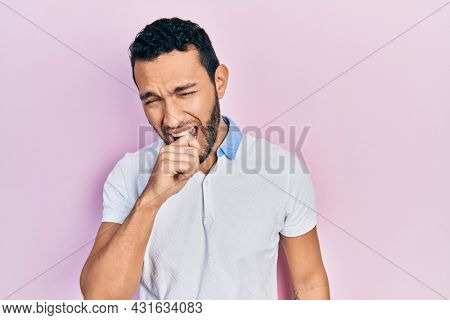 Hispanic man with beard wearing casual white t shirt feeling unwell and coughing as symptom for cold or bronchitis. health care concept.